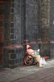 Kvinna i rullstolen som säljer stearinljus på domkyrkan i Banos, Ecuador Arkivfoto