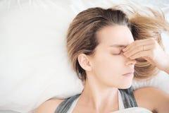 Kvinna i säng med allergi eller huvudvärk royaltyfri foto