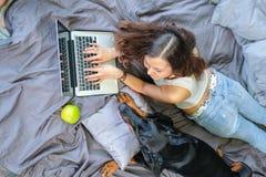 Kvinna i säng med den stora hunden Arkivbild