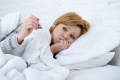 kvinna i säng med för febrig svag viruset för influensa lidandevinter för termometer den kalla royaltyfri bild