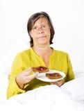 Kvinna i säng med rostat bröd Fotografering för Bildbyråer