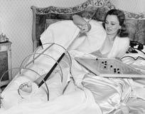 Kvinna i säng som försöker att skrapa hennes brutna fot med en pol (alla visade personer inte är längre uppehälle, och inget gods Royaltyfri Bild