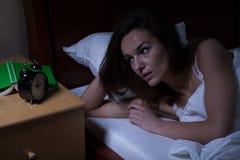 Kvinna i säng som ser klockan arkivbild