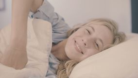 Kvinna i säng som vaknar sträckning upp och ler på kameran arkivfilmer