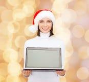 Kvinna i santa hjälpredahatt med bärbar datordatoren Arkivfoto
