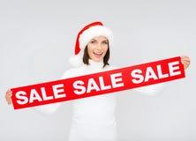 Kvinna i santa hjälpredahatt med det röda försäljningstecknet Arkivfoton