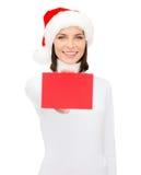 Kvinna i santa hjälpredahatt med det tomma röda kortet Arkivfoton