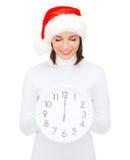 Kvinna i santa hjälpredahatt med klockan som visar 12 Royaltyfri Foto