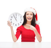 Kvinna i santa hjälpredahatt med klockan som visar 12 Arkivfoto