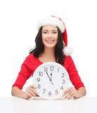Kvinna i santa hjälpredahatt med klockan som visar 12 Fotografering för Bildbyråer