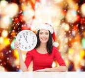 Kvinna i santa hjälpredahatt med klockan som visar 12 Arkivbild