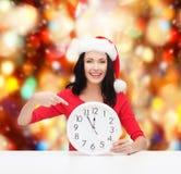Kvinna i santa hjälpredahatt med klockan som visar 12 Royaltyfri Bild