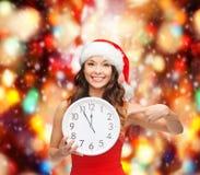 Kvinna i santa hjälpredahatt med klockan som visar 12 Arkivbilder