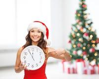 Kvinna i santa hjälpredahatt med klockan som visar 12 Arkivfoton