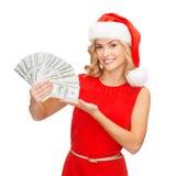 Kvinna i santa hjälpredahatt med oss dollarpengar Arkivbild
