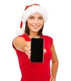 Kvinna i santa hjälpredahatt med smartphonen Arkivfoto