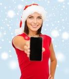 Kvinna i santa hjälpredahatt med smartphonen Royaltyfri Foto