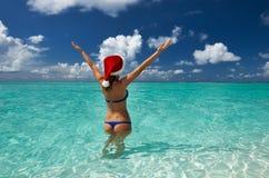Kvinna i santas hatt på stranden Arkivfoton
