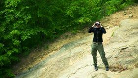Kvinna i skog med kikare Arkivfoton