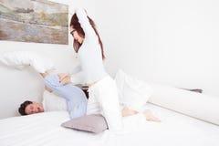 Kvinna i slående man för pyjamas med kudden medan honom  Royaltyfri Foto