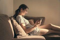 Kvinna i slags tvåsittssoffahemkläder som kopplar av på minnestavlan och läsning för soffa den hållande Fotografering för Bildbyråer