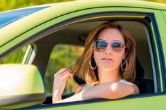 Kvinna i solglasögon bak hjulet Royaltyfria Bilder