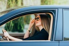 Kvinna i solglasögon bak hjulet Royaltyfria Foton