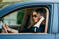 Kvinna i solglasögon bak hjulet Royaltyfri Foto