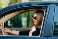 Kvinna i solglasögon bak hjulet Arkivfoton