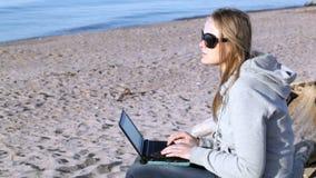 Kvinna i solglasögon genom att använda bärbara datorn på stranden