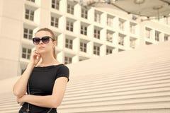 Kvinna i solglasögon som poserar på trappa och bygger i Frankrike arkivbild