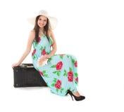 Kvinna i sommarklänning med hatt- och pengarsammanträde på ett svart fall royaltyfria bilder