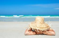 Kvinna i sommarsugrörhatt på stranden på bakgrundshavet Fotografering för Bildbyråer
