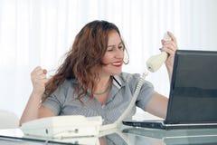 Kvinna i sp?nning framme av datoren royaltyfria bilder