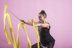 Kvinna i sport, flickadansare med det klipska bandet, slank gymnast som poserar på rosa bakgrund Royaltyfria Foton