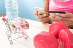 Kvinna i sportactivewear genom att använda mobiltelefonen och kreditkort för arkivbild