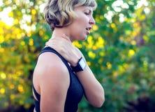 Kvinna i sportswearen som trycker på hennes hals vid smärtsam skada, över a royaltyfria bilder