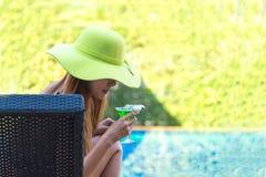 Kvinna i stor hatt som kopplar av på simbassängen, nära havet Fotografering för Bildbyråer