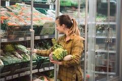 Kvinna i supermarket Den h?rliga unga kvinnan rymmer i nya organiska gr?nsaker f?r h?nder och ?ppnar kylen i supermarket royaltyfria bilder