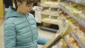 Kvinna i supermarket Tillbaka sikt av den unga caucasian kvinnan i det blåa omslaget som väljer brödbagetten som sätter det i vag arkivfilmer