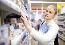 Kvinna i supermarketen. Arkivfoton