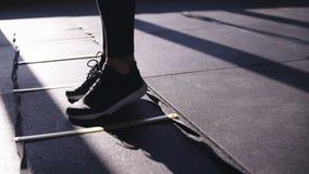Kvinna i svart damasker som utbildar på idrottshallen, medan kliva, tillbaka och framåtriktat på delade avsnitt på golvövningen arkivfilmer