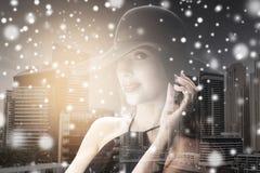 Kvinna i svart hatt över stadsbakgrund och snö Royaltyfria Bilder