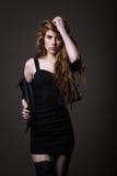 Kvinna i svart klänning, läderomslag och strumpor Fotografering för Bildbyråer