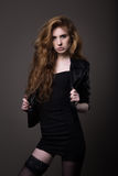 Kvinna i svart klänning, läderomslag och strumpor Royaltyfri Fotografi