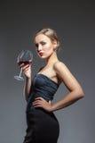Kvinna i svart klänning med vinexponeringsglas Royaltyfria Bilder