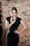 Kvinna i svart klänning på bakgrund för tegelstenvägg elegans Tystnad royaltyfri bild