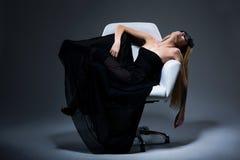 Harmoni & Sensuality. Romantiskt blont kvinnligt i den svart klänningen som vilar i fåtölj. Tillfredsställelse royaltyfri fotografi