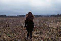 Kvinna i svart laganseende i kallt höstfält Royaltyfri Foto