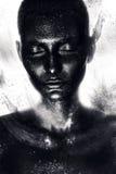 Kvinna i svart målarfärg i damm Arkivbilder